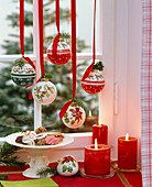 Christmas tree balls with Nordic motifs, hanging in the window