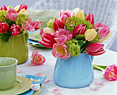 Bouquet of tulipa and viburnum in blue pitcher
