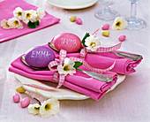 Table decoration with primula on pink folded napkins