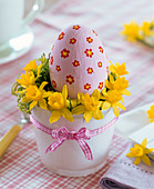 Easter egg with painted flowers in wreath of Narcissus (Daffodil)