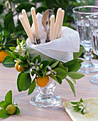 Kranz aus Citrofortunella (Calamondinorange) um Glas mit Serviette