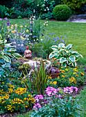 Woman sculpture on stone with Sempervivum (houseleek) in flowerbed