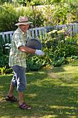 Mann düngt Rasen