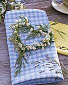 Convallaria and grasses wreath in heart shape on napkin