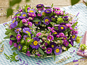 Blue-violet wreath of autumnal branches and summer asters