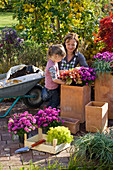 Mother and daughter planting terracotta tubs