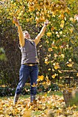 Woman throws leaves in the air
