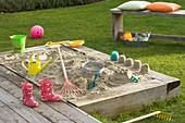 Sandbox with toys and kids rubber boots