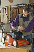 Man maintains lawnmower