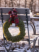 Moss wreath in hoarfrost with checkered bow