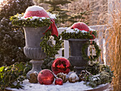 Snow-covered and frosted amphorae with wreaths of Buxus