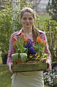 Young woman with Tulipa 'Flair', Hyacinthus 'Kronos'
