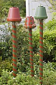 Colorful painted clay pots on pylons as beneficial shelter