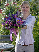Young woman with bouquet of callistephus (summer aster), Erigeron