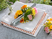 Cutlery in a flower wreath made of marigold, roses and chamomile