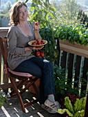 Woman enjoying freshly picked tomatoes on the balcony
