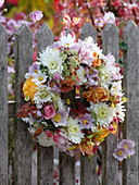 Autumnal flower wreath at the fence