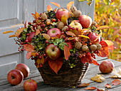 Autumn bouquet with apples, nuts, leaves and hydrangea