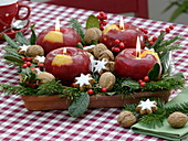 Unusual Christmas wreath with apple candles on square saucer