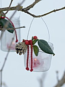 Jam jars hung as lanterns with wire on branch