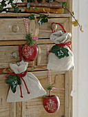 Linen bags with numbered ivy leaves and decorative wooden apples