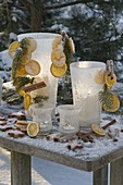 Frozen glasses with slices of orange, cinnamon sticks, picea