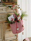 Red and white checkered bag with chocolate St. Nicholas, tea towel, Pinus