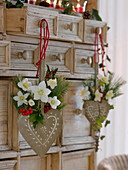 Small bouquets of Helleborus and Ilex in heart vases to hang