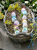 Basket with hay as Easter basket, eggs with 'Frohe Ostern' message
