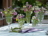 Small meadow flower bouquets in glasses