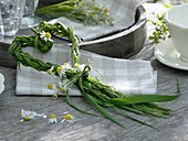 Braided heart of grasses with chamomile flowers