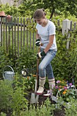 Young woman planting summer flower bed
