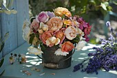Mixed bouquet of fragrant roses in metal pails