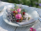 Small bouquet made of raspberries (Rubus), pink (rose), gypsophila