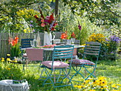 Table with gladiolus-dahlia bouquet under apple tree