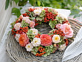 Late summer wreath made of pink (rose), sorbus (rowanberry)