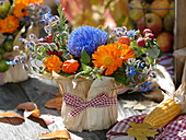 Thanksgiving arrangement stuck in yoghurt pail with corn leaves