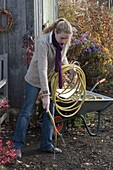 Woman emptying garden hose for wintering