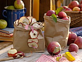 Paper bags with apples and dried apple slices (Malus)
