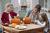 Mother with daughters makes pumpkin heads