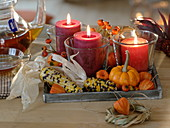 Candles in glasses on wooden tray, decorated with colorful corn