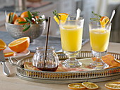 Hot orange juice in grog glasses, pieces of orange