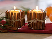 Candles in glasses covered with cinnamon sticks