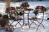Verschneite Terrasse weihnachtlich geschmückt mit Strauß aus Ilex