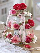 Homemade cake stand made of plates and cups with roses and carnations