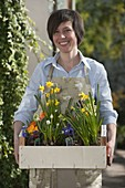 Woman with fruit box full of spring bloomers