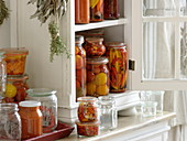 Small cupboard with cooked tomatoes in vinegar, hot peppers and tomato sugo