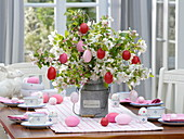 Easter table decoration with a bouquet of apple blossom branches