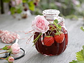 Glass with strawberry jam, decorated as a gift
