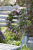 Wreath of grasses and trifolium pratense (red clover) on the back of the chair